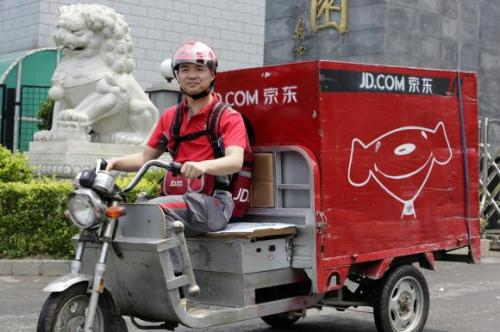Liu, CEO and founder of China's e-commerce company JD.com, rides an electric tricycle as he makes a delivery run in Beijing